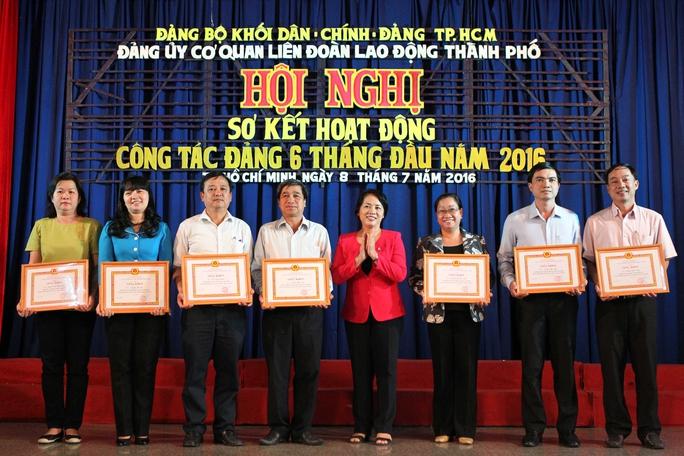 Bà Trần Kim Yến, Bí thư Đảng ủy Cơ quan LĐLĐ TP, tặng giấy khen cho các đảng viên hoàn thành xuất sắc nhiệm vụ trong năm 2015 Ảnh: QUANG LIÊM