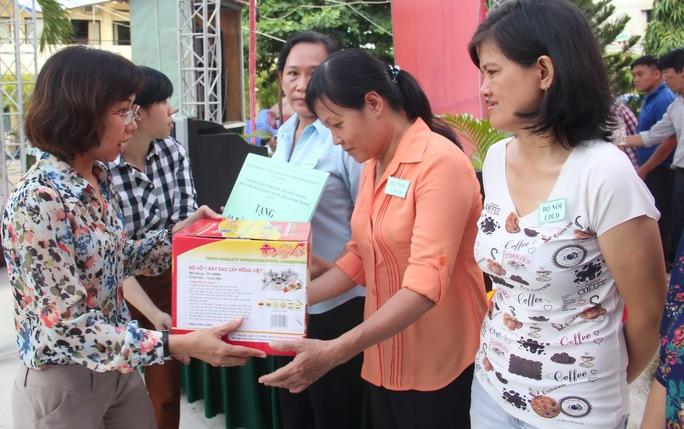Bà Huỳnh Thị Ngọc Liên, Trưởng Ban Nữ công LĐLĐ TP HCM, trao vật dụng cho các gia đình khó khăn
