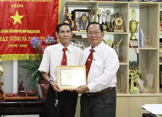 Leg: Ông Tạ Long Hỷ (bìa phải), Phó tổng giám đốc Vinasun, trao giấy khen và tiền thưởng cho tài xế Bình