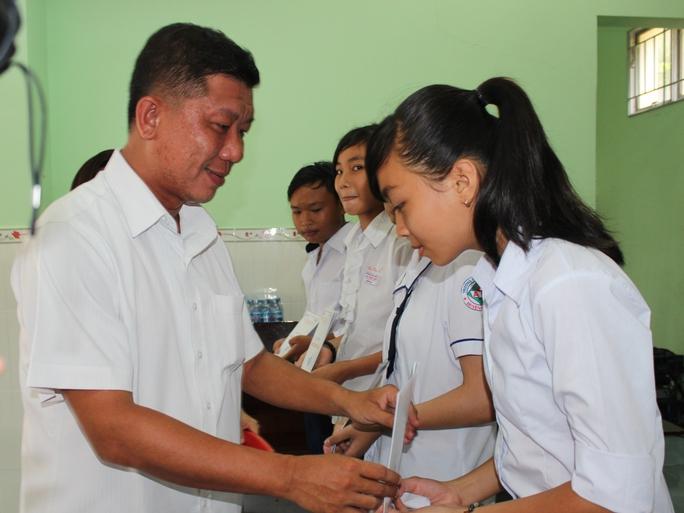 Ông Trần Đoàn Trung, Phó Chủ tịch LĐLĐ TP HCM, trao học bổng Nguyễn Hữu Thọ cho học sinh, sinh viên nghèo Ảnh: THANH NGA