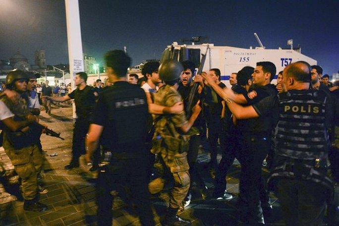 Binh sĩ đảo chính bị người dân bắt giao cho cảnh sát ở quảng trường Taksim (Istanbul) hôm 15-7. Ảnh: AP