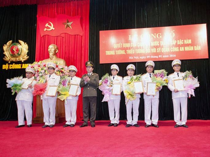Đại tướng Trần Đại Quang trao Quyết định của Chủ tịch nước và tặng hoa chúc mừng các sĩ quan công an được thăng cấp bậc hàm cấp Tướng - Ảnh: Cổng TTĐT Bộ Công an