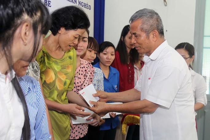 Ông Đặng Ngọc Tùng, nguyên Chủ tịch Tổng LĐLĐ Việt Nam, trao quá cho công nhân khó khăn tại huyện Nhà Bè Ảnh: HOÀNG TRIỀU