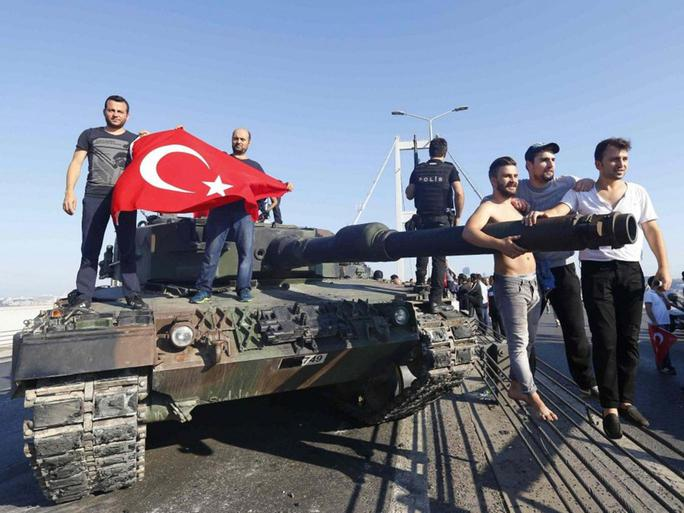 Người dân Thổ Nhĩ Kỳ đứng bên chiếc xe tăng do quân đảo chính bỏ lại. Ảnh: Reuters