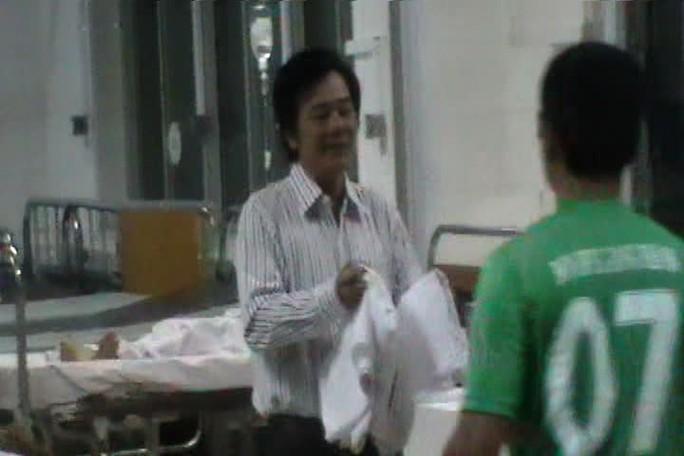 PGS - TS Tạ Văn Trầm lấy drap trải cho bệnh nhân sau vụ hỏa hoạn