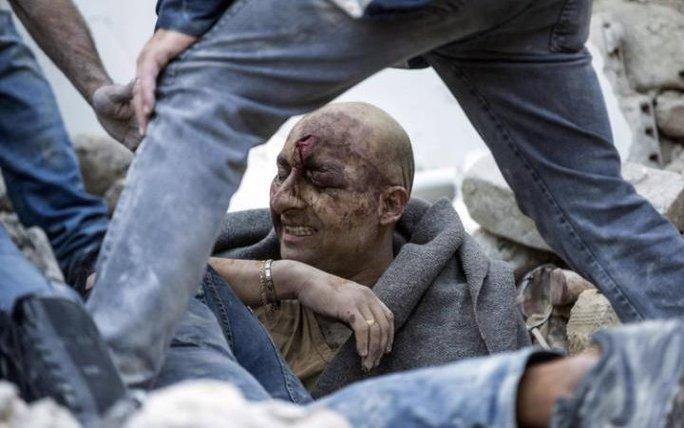 Một người sống sót được kéo ra khỏi đống đổ nát ở thị trấn Amatrice. Ảnh: Telegraph