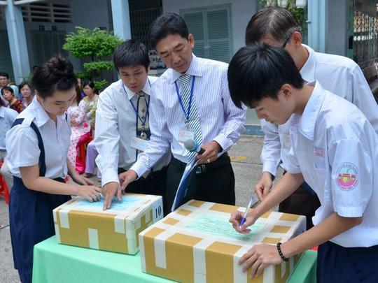 Học sinh ở trường THCS Chu Văn An, quận 11 kiểm tra đề thi văn. Ảnh: Tấn Thạnh