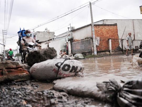 Để ngăn nước ô nhiễm từ đường tràn vào nhà, các hộ dân dùng bao cát chắn trước cửa nhà nhưng nước vẫn tràn vào mỗi khi có xe tải chạy ngang qua.