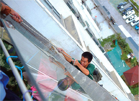 Hanging by a rope: Mr Liu was left dangling eight storeys above ground before he was rescued by firemen