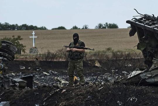 Một phiến quân ly khai đứng giám sát tại hiện trường vụ MH17 bị rơi. Ảnh: AP