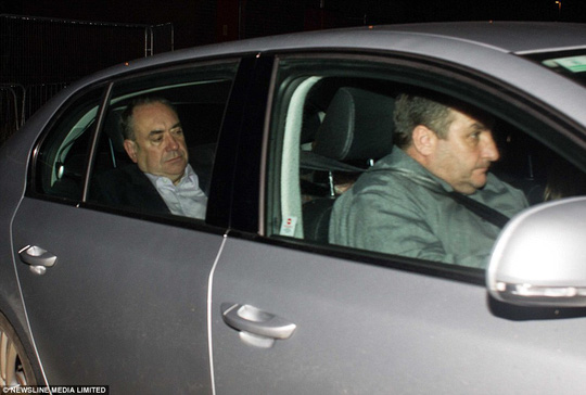 On the run: Ashen-faced First Minister Alex Salmond looked miserable as he was driven through a side gate at Aberdeen airport tonight, before boarding a private jet