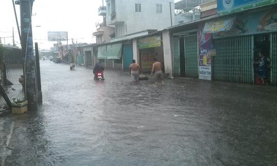 Nước ngập sâu trên Quốc lộ 13, quận Thủ Đức (TP HCM).