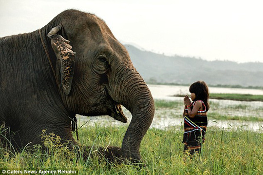 Kim Luan (right) plays with her pet elephant, which helps to transport goods and work the fields