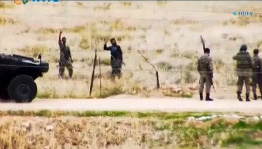 Bravado: After several minutes chatting, the militants wander off, defiantly raising their index finger to the sky to represent jihadism while chanting Allahu Akbar - a phrase that translates as God is the greatest