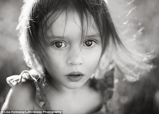 Entrancing: Lisa Holloway, who is based with her husband in rural Arizona, is entirely self-taught and uses only natural light to photograph her children. Pictured, Camille, six