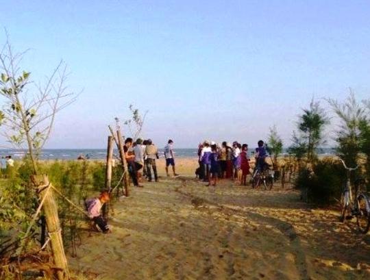 Người dân đứng ở bờ biển ngóng chờ lực lượng cứu hộ tìm kiếm thi thể cháu Thành