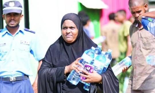 Một người dân Maldives nhận nước uống miễn phí hôm 6-12. Ảnh: AP