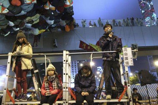 Thủ lĩnh biểu tình học sinh Hoàng Chi Phong (phải) cho biết nhóm của anh sẽ duy trì nguyên tắc bất bạo động suốt thời gian cảnh sát tiến hành dọn dẹp. Ảnh: Reuters