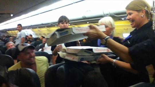 Phi hành đoàn phát pizza cho hành khách. Ảnh: CNN