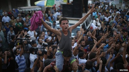 Người dân Palestine ở Gaza đổ ra đường ăn mừng thỏa thuận ngừng bắn. Trong khi đó, người dân Israel vẫn tỏ ý hoài nghi. Ảnh: Reuters