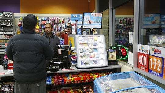 Employee Gurcharam Sohel, center, helps customer, this store sold one of the $400 million lottery ticket at Dixon Landing gas station in the Food Mart in