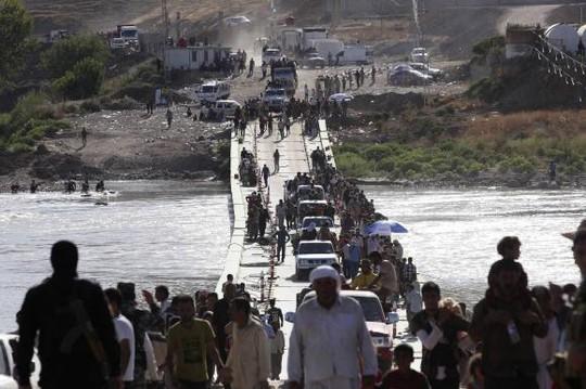 Nhiều người Yazidi quay trở lại Iraq sau khi trốn thoát khỏi thị trấn Sinjar hôm 10-8. Ảnh: Reuters