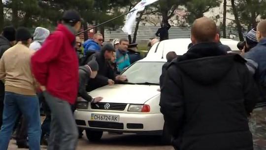 Người biểu tình thân Nga đập phá xe hơi ở thành phố Sevastopol hôm 9-3. Ảnh: BBC