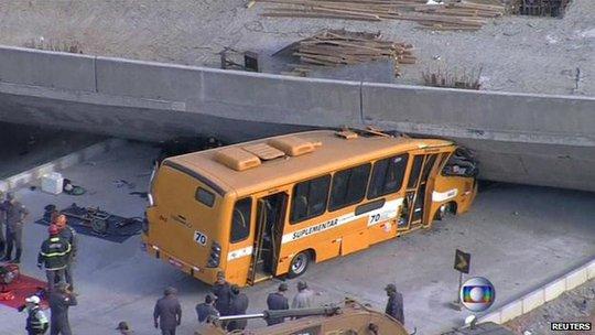 Chiếc xe buýt màu vàng bị đè nát phần đầu. Ảnh: Reuters