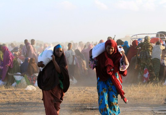 Phụ nữ Somalia nhận đồ ăn gần một thị trấn phía bắc thủ đô Mogadishu tháng 12-2013. Ảnh: Reuters