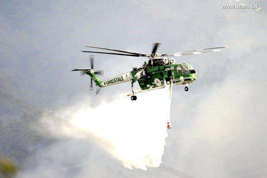 Trực thăng phun nước dập lửa nơi 2 chiếc máy bay bốc cháy. Ảnh: News.cn