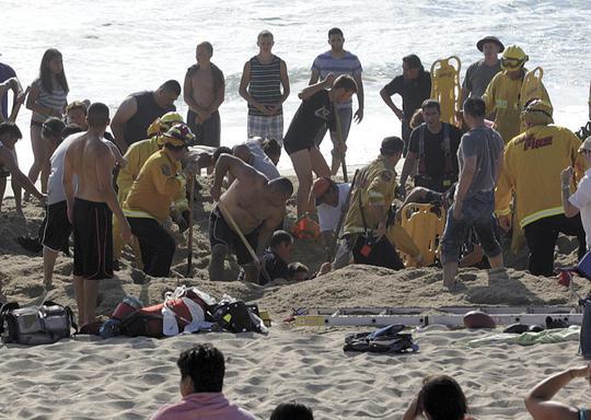 30 người có mặt tại bãi biển tích cực đào bới cứu chàng trai nhưng không kịp. Ảnh: AP