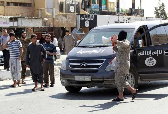 Một chiến binh IS thông báo đã chiếm được căn cứ không quân Taqba ở thành phố cùng tên hôm 24-8. Ảnh: Reuters
