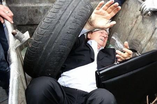 Ông Vitaly Zhuravsky bị nhét vào thùng rác. Ảnh: Twitter