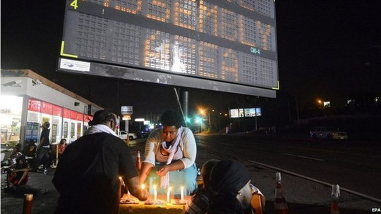Demonstrators light candles while taking a break from walking at the approved assembly area set up for them while they protest the shooting death of Michael Brown in Ferguson, Missouri, USA, late 20 August 2014