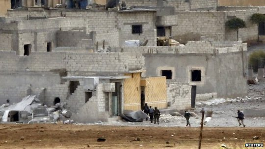 Unidentified armed men run through the Syrian town of Kobane (15 October 2014)