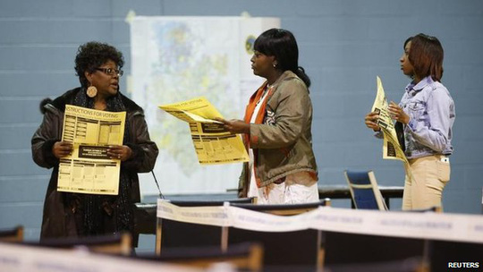 Voters assess the options as they queue in Charlotte, North Carolina, 4 Nov