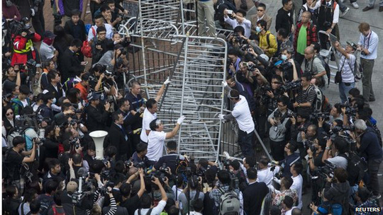 Building employees dismantle a barricade outside Citic Tower in accordance with a court injunction to clear up part of the protest site, outside the government headquarters in Hong Kong 18 November 2014.