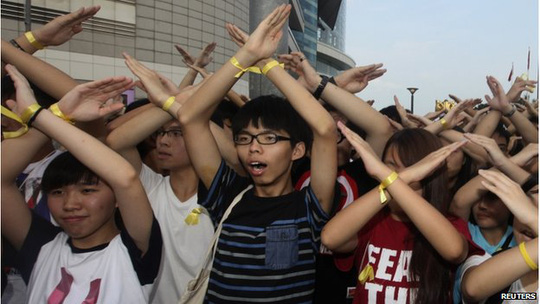 Scholarism founder Joshua Wong (C) and other members chant slogans during a flag raising ceremony in Hong Kong 1 October 2014, celebrating the 65th anniversary of China National Day