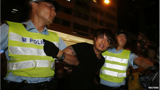 An anti-Occupy Central protester is detained by policemen after he broke through a cordon line, trying to charge pro-democracy protesters, at Hong Kongs shopping Mong Kok district, where a main road is occupied, 3 October 2014.