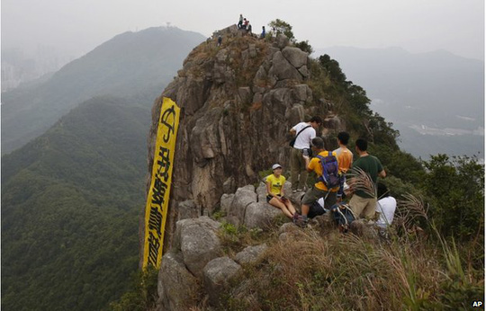 Hikers take pictures of the yellow banner with the words reading: I want genuine universal suffrage in Chinese and Umbrella Movement in English hanging from the face of Lion Rock mountain in Hong Kong Thursday, 23 October 2014