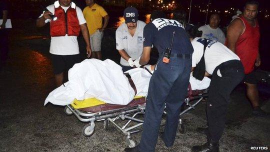 Thi thể chàng thiếu niên 17 tuổi được đưa vào bờ, còn cha cậu vẫn mất tích. Ảnh: Reuters