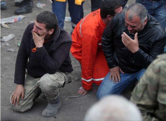 Những người đàn ông chờ ngoài hầm mỏ. Ảnh: AP