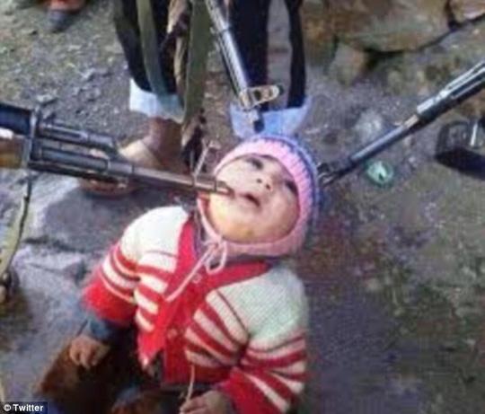 Bức ảnh đứa trẻ quỳ gối và bị ba họng súng trường chĩa vào đầu đang gây bão trên mạng internet. Ảnh: Twitter
