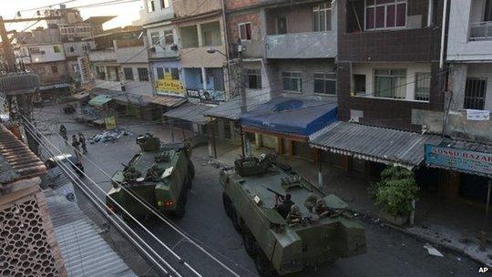 Quân đội Brazil và xe bọc thép áp sát khu ổ chuột Mare sáng sớm 30-3. Ảnh: AP