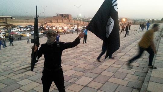 Một chiến binh ISIL trên đường phố Mosul - Iraq. Nhóm này vừa hành quyết đóng đinh 8 tù nhân tại Syria. Ảnh: Reuters