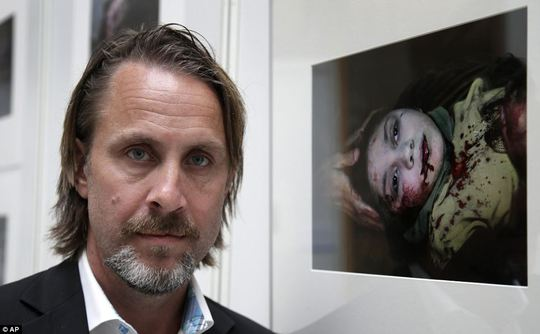Award: Niclas Hammarstrom from Sweden poses in front his photograph, the winner of Unicef Photo of the Year 2013, which he captured while spending 24 hours documenting the work of medics at Dar-al-Shifa hospital. The photo shows Danias head being cradled in her oldest brothers hands while her wounds are dressed