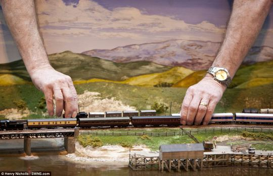 Impressive: Two people hold on to handcrafted miniature models of trains, which were showcased at the annual Miniatura exhibition and trade show over the weekend