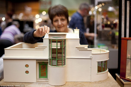 Modern style: They added: Its always good to get the Miniatura Buzz! Above, a woman poses with a cream-and-white house, which stands at just a few inches tall