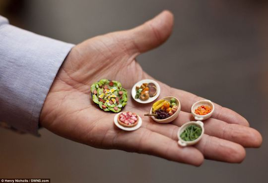 Appealing: The show is now one of the worlds biggest miniature events. Above, a man holds an array of handcrafted food dishes, including bowls of carrots and fruit