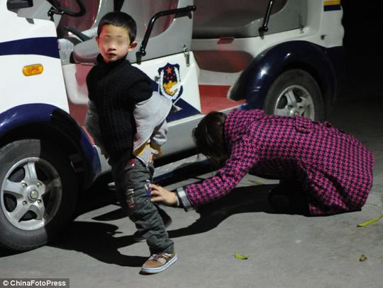 A mother cries as she intends to give up her child. Abandoning children is illegal in China, but the hatches were introduced so parents could abandon infants safely rather than leaving them in the streets